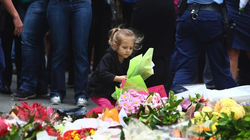 A girl lays flowers in a makeshift memorial near the site where a gunman held hostages for 16 hours at a popular Sydney cafe, Australia, Tuesday, Dec. 16, 2014. The siege ended early Tuesday with a barrage of gunfire that left two hostages and the Iranian-born gunman dead, and a nation that has long prided itself on its peace rocked to its core. (AP Photo/Steve Christo)