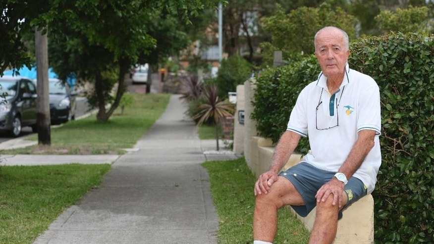 John O'Brien, one of hostages of the Sydney cafe siege, poses for a photo as he relaxes in his front yard in Sydney, Australia, Wednesday, Dec. 17, 2014. O'Brien, 82, was the first hostage to escape the Lindt Chocolat Cafe after a gunman took 17 people hostage on Monday Dec. 15. Three people including the gunman were shot after police ended the siege at the coffee shop early Tuesday. (AP Photo/Rob Griffith)