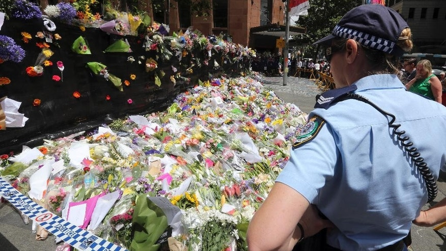 A police officer looks at flower tributes placed at a temporary memorial site close to the Lindt Chocolat Cafe in the central business district of Sydney, Australia, Wednesday, Dec. 17, 2014. Three people including the gunman were shot after police ended the siege in the coffee shop early Tuesday. Australia's prime minister acknowledged Wednesday that the nation's security system failed to keep track of a gunman responsible for the deadly siege, and promised a transparent investigation into why the man was not on any terror watch list despite having a long criminal history. (AP Photo/Rob Griffith)