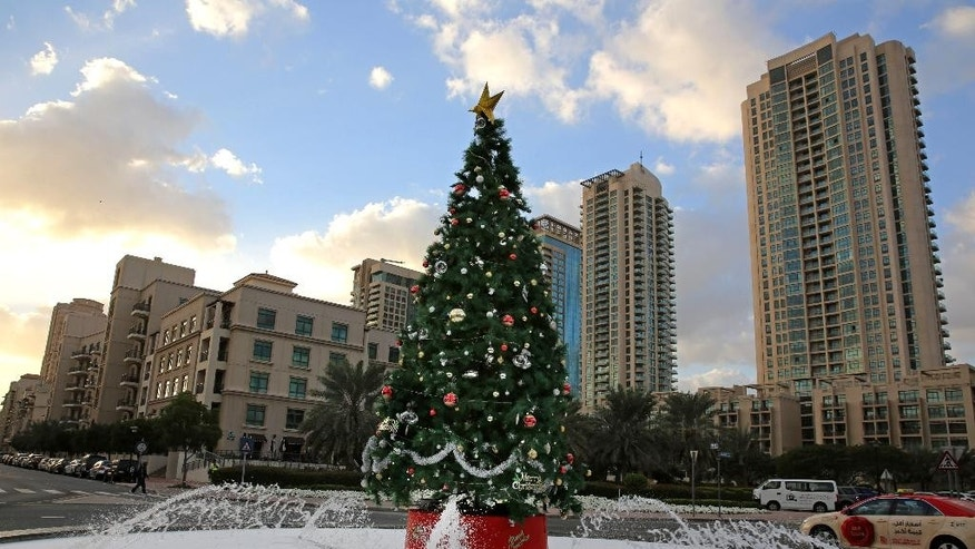 "FILE - In this Saturday, Dec. 21, 2013 file photo, a large Christmas tree with fake snow around it, is showcased on a street in Dubai, United Arab Emirates. Britain wants to make sure its citizens are more nice than naughty while soaking up the Persian Gulf sun this holiday season. A social media campaign by British Embassy staff in the United Arab Emirates running in December, 2014 is a play on the classic poem ""'Twas the Night Before Christmas,"" and includes travel advice aimed at keeping unwitting Britons out of trouble. (AP Photo/Kamran Jebreili, File)"