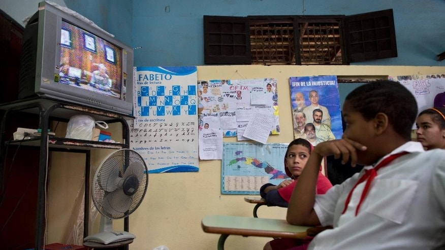 "Students watch a live, nationally broadcast speech by Cuba's President Raul Castro about the country's restoration of relations with the United States, on a TV at school in Havana, Cuba, Wednesday, Dec. 17, 2014. Castro said profound differences remain between Cuba and the U.S. in areas such as human rights, foreign policy and questions of sovereignty, but that the countries have to learn to live with their differences ""in a civilized manner."" (AP Photo/Ramon Espinosa)"