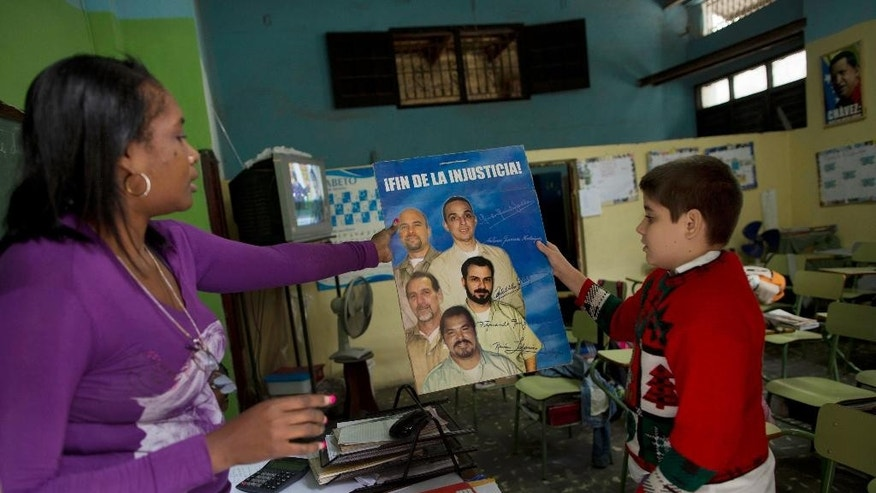 "A teacher hands a student a poster of ""The Cuban Five"" to hang on their classroom wall in Havana, Cuba, Wednesday, Dec. 17, 2014. The men, who are hailed as heroes in Cuba, were convicted in 2001 in Miami on charges including conspiracy and failure to register as foreign agents in the U.S. On Wednesday, Dec. 17, 2014, three of the five Cubans were released by the U.S. in exchange for U.S. citizen Alan Gross and an unnamed Cuban man who was imprisoned for nearly 20 years for spying for the United States. Two of the Cuban Five had previously been released after finishing their sentences. (AP Photo/Ramon Espinosa)"