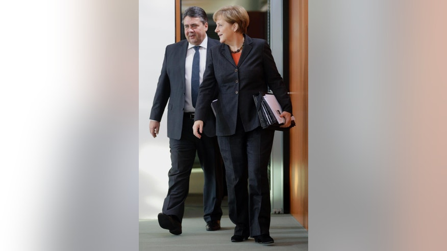German Chancellor Angela Merkel, right, and German Economy and Energy Minister Sigmar Gabriel, left, arrive for the weekly cabinet meeting at the chancellery in Berlin, Germany, Wednesday, Dec. 17, 2014. (AP Photo/Michael Sohn)