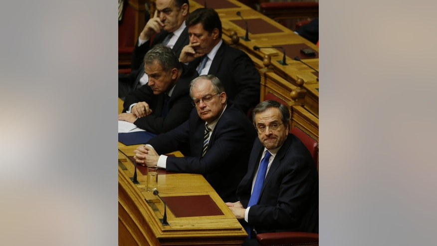Greece's Prime Minister Antonis Samaras, foreground, attends with his ministers the first round of voting to elect a new Greek president at the Parliament in Athens, Wednesday, Dec. 17, 2014. Parliament has failed to elect a new Greek president in the first round of voting, leaving another two tries before the government falls and early elections have to be called. The conservative-led government's candidate, former European Commissioner Stavros Dimas, received 160 votes Wednesday, far short of the 200 needed for an outright win. (AP Photo/Thanassis Stavrakis)