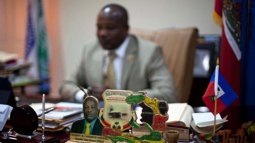 "A photograph of Senate President Simon Dieseul Desras sits on his desk during an interview at his office in Port-au-Prince, Haiti, Wednesday, Dec. 17, 2014. ""We need a new government as soon as possible,"" Desras said. ""I think it's a complex and politically turbulent moment in Haiti."" Desras said that while his name is apparently on the list of candidates for interim prime minister, he doesn't know yet if he would seek the position. Haiti's President Michel Martelly met Wednesday with opposition leaders in a bid to stabilize the politically fractious country as pressure mounted on him to appoint an interim prime minister. (AP Photo/Dieu Nalio Chery)"