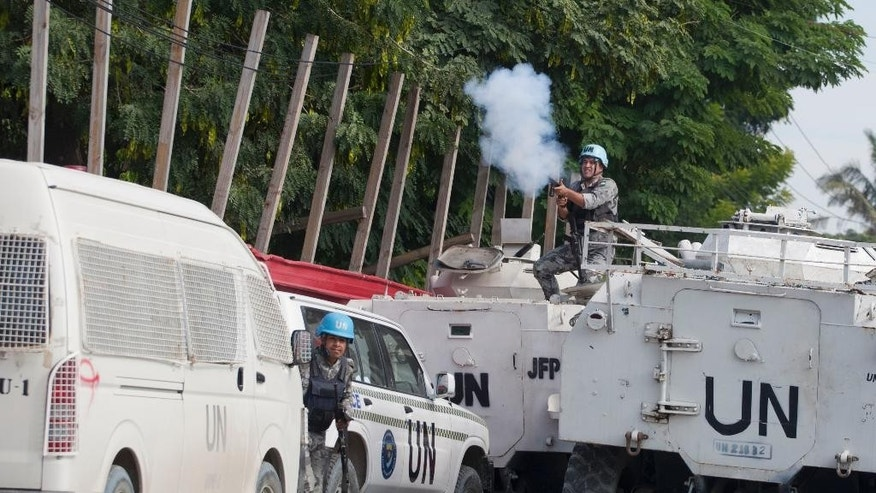 A Jordanian soldier from the U.N. peacekeeping force fires tear gas at anti-government protesters demanding the resignation of Haiti's President Michel Martelly and Prime Minister Laurent Lamothe in Port-au-Prince, Haiti, Friday, Dec. 12, 2014. The protest occurred hours before Martelly was scheduled to talk about a commission report that calls for a new consensus government. (AP Photo/Dieu Nalio Chery)