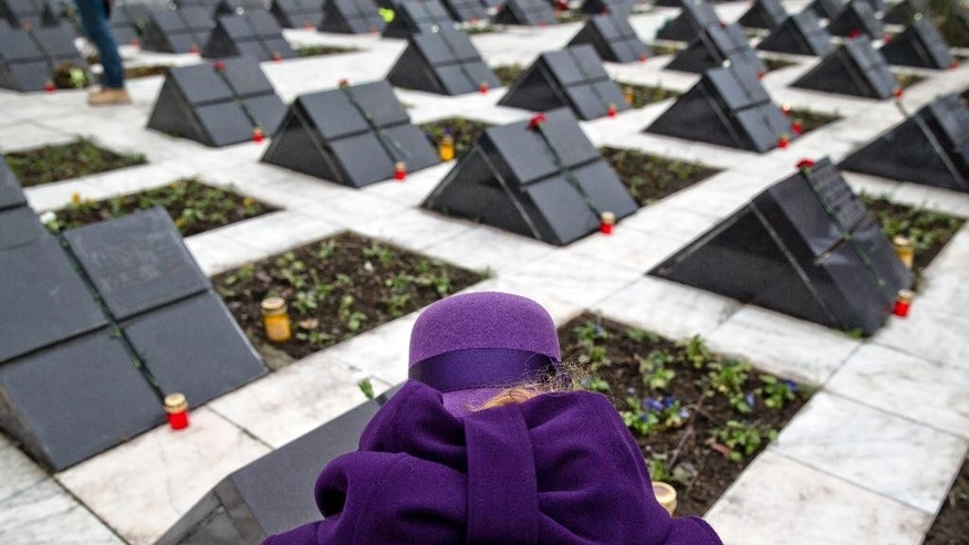 A woman lights candles by gravestones during a religious service for those killed in the anti-communist uprising 25 years ago, at the Heroes cemetery, in Timisoara, Romania, Wednesday, Dec. 17, 2014. The uprising, which left many thousands dead, and ended the rule of dictator Nicolae Ceausescu, who was executed, started in the western Romanian town of Timisoara on Dec. 16, 1989 and the first people died on Dec. 17, 2014.(AP Photo/Vadim Ghirda)