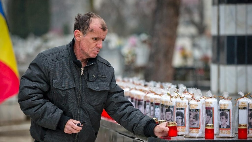 Candles with pictures and names of revolution victims are placed on a monument during a religious service for those killed in the anti-communist uprising 25 years ago, at the Heroes cemetery, in Timisoara, Romania, Wednesday, Dec. 17, 2014. The uprising, which left many thousands dead, and ended the rule of dictator Nicolae Ceausescu, who was executed, started in the western Romanian town of Timisoara on Dec. 16, 1989 and the first people died on Dec. 17, 2014.(AP Photo/Vadim Ghirda)