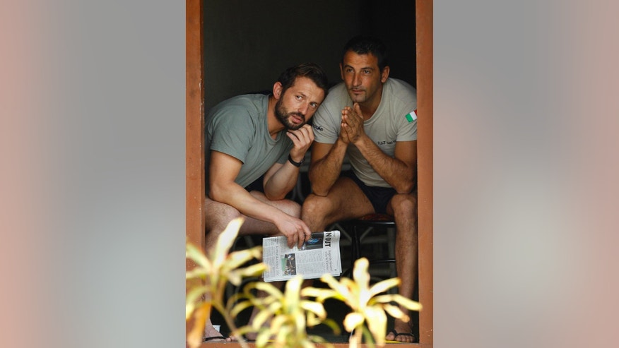 "FILE - In this Feb. 27, 2012 file photo, Italian marines Salvatore Girone, left, and Massimiliano Latorre look out as they sit in the doorway of a government guest house where they are being held by Indian authorities, in Kochi, India. Italy says a marine who suffered a stroke while detained in India is too ill to return, deepening the diplomatic flap over the 2012 shooting death of two Indian fishermen. Defense Minister Roberta Pinotti said Wednesday, Dec. 17, 2014 Massimiliano Latorre's health is the ""priority.'"" Expressing irritation and disappointment, Pinotti told Italian lawmakers: ""Conditions aren't there to let Latorre leave Italy."" Latorre is one of two Italian marines detained by India while assigned to anti-piracy duty aboard an Italian cargo ship. No formal charges have been lodged. (AP Photo/Aijaz Rahi, File)"