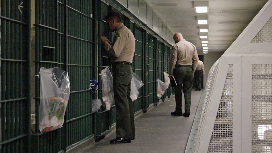 FILE - In this Oct. 3, 2012, file photo, Los Angeles County Sheriff's deputies inspect a cell block at the Men's Central Jail in downtown Los Angeles. The nationâs largest sheriffâs department agreed to federal court oversight and will adopt a new use-of-force policy to settle a class-action lawsuit brought by jail inmates who said they were beaten by guards. The agreement, in effect a consent decree, was approved Tuesday, Dec. 16, 2014, by the Los Angeles County Board of Supervisors. It is the latest in several efforts to reform the scandal-plagued department beset with allegations of rampant abuse by deputies, costly lawsuits and federal convictions of deputies for obstructing an FBI probe into jail beatings. (AP Photo/Reed Saxon, File)