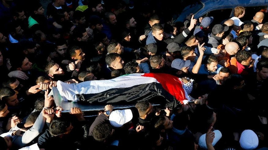 Palestinians  carry the body of 20-year-old Mahmoud Abdalla Mahmoud Abdalla, who was killed in clashes with Israeli troops, during his funeral in the Qalandia refugee camp near the West Bank city of Ramallah, Tuesday, Dec. 16, 2014. The Israeli military said Palestinians threw explosive charges and opened fire at soldiers during an arrest operation and that they responded with fire of their own, killing one man, and wounding another.(AP Photo/Majdi Mohammed)