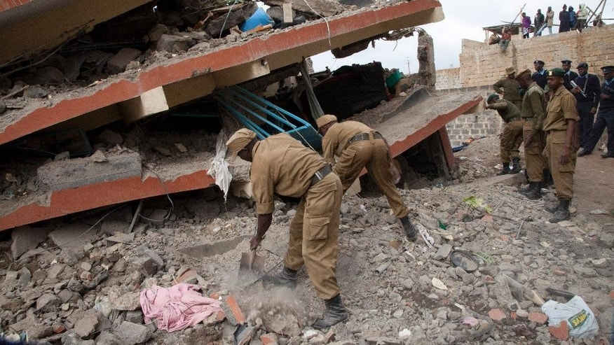 Rescue workers clean the path to rescue people trapped after a building collapsed in Nairobi, Kenya Wednesday, Dec. 17, 2014. (AP Photo/Sayyid Azim)