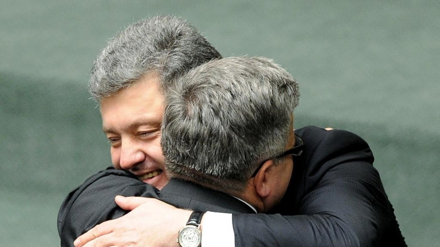 Ukrainian President Petro Poroshenko left, hugs his Polish counterpart Bronislaw Komorowski after addressing lawmakers at the Polish parliament in Warsaw, Poland, Wednesday, Dec. 17, 2014, on the first day of his official visit to Poland. (AP Photo/Alik Keplicz)