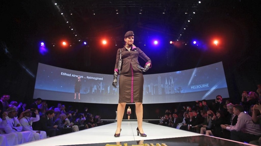 An Etihad Airways stewardess presents its new uniform in a fashion show style as the airline company unveils the launch of the Airbus A380 and Boeing 787 during an event in Abu Dhabi, United Arab Emirates, Thursday, Dec. 18, 2014. (AP Photo/Kamran Jebreili)