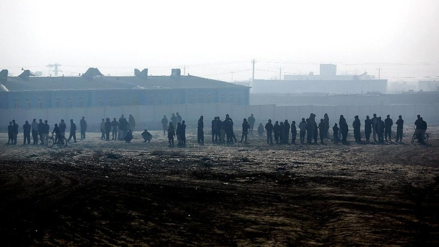 Afghan residents stand near the site of a suicide attack in Kabul, Afghanistan, Thursday, Dec. 18, 2014. An Afghan official says a suicide bomber detonated his vehicle as it was being followed by police on the outskirts of the capital Kabul, killing a police officer and wounding several. (AP Photo/Massoud Hossaini)