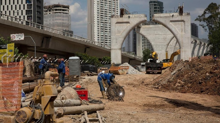 "In this Wednesday, Dec. 17, 2014 photo, men work on the construction of the monorail line, which is part of the city's subway system, in Sao Paulo, Brazil. In Sao Paulo, prosecutors accuse 33 businessmen of running a ""cartel"" to profit from the city's subway system. Brazil is witnessing an unprecedented flurry of legal activity, provoked by a growing middle class whose anger over corruption erupted in protests last year, and independent agencies increasingly capable of handling complex probes. (AP Photo/Andre Penner)"