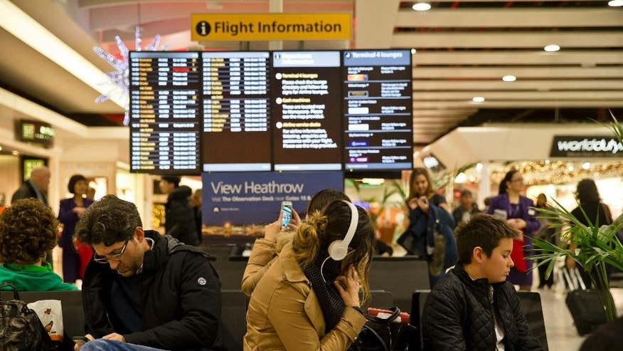 Passengers wait at Heathrow Airport in London, Friday, Dec. 12, 2014. London's airspace was closed today due to what authorities say was a computer failure at one of Britain's two air traffic control centres. Britain's national air traffic body says the computer problem that touched off troubles in the system has been fixed and it is in the process of returning to normal operations.  (AP Photo/Vadim Ghirda)