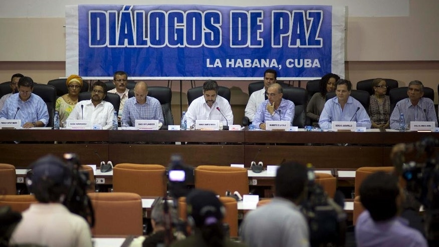 "FILE - In this May 16, 2014 file photo, negotiators from the Revolutionary Armed Forces of Colombia (FARC), left, and Colombia's government, right, give a press conference under a sign that reads in Spanish ""Peace Talks"" in Havana, Cuba. Colombia's government has rebuffed a unilateral truce declared on Wednesday, Dec. 18, 2014 by the country's largest rebel group, saying conditions demanded by the guerrillas' are unacceptable until a peace deal is reached. Sitting at the table, from left, are chief of the western bloc of the FARC Pablo Catatumbo, FARC chief negotiator Ivan Marquez, Norwegian guarantor Dag Nylander, Cuban guarantor Rodolfo Benitez Verson, head of Colombia's government team Humberto de la Calle, government negotiator Sergio Jaramillo, and government negotiator Gen. Jorge Mora. (AP Photo/Ramon Espinosa, File)"