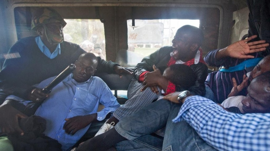 A small group of protesters against the new security law, who managed to get past heavy police cordons preventing demonstrations, react as they are beaten with wooden clubs inside the back of a police pickup truck after being arrested for shouting against the new law, seen through the plastic window of the truck, outside the Parliament building in Nairobi, Kenya Thursday, Dec. 18, 2014. Kenyan legislators Thursday exchanged blows on changes to security laws which the government says will help fight terrorism but which critics say are meant to silence dissent by curtailing civil liberties, with opposition legislators throwing the papers on the floor and government supporters hitting and tearing the clothes of an opposition senator. (AP Photo/Ben Curtis)