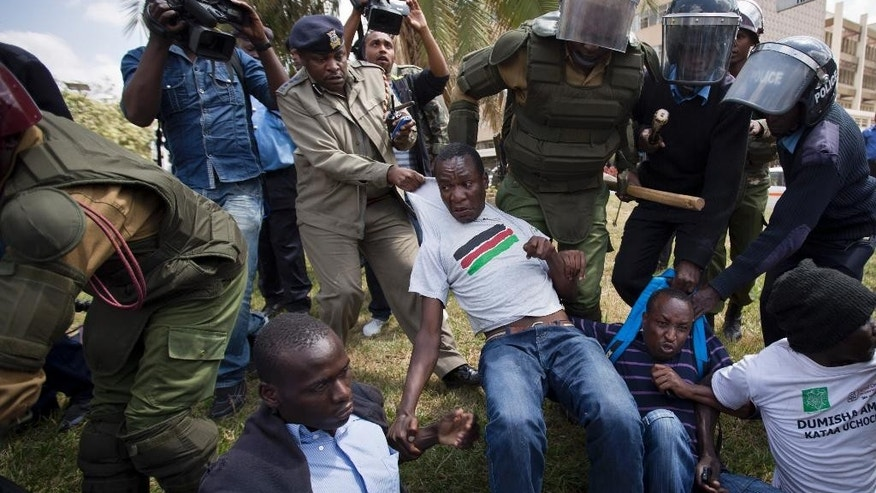 A small group of protesters against the new security law, who managed to get past heavy police cordons preventing demonstrations, are beaten with wooden clubs and arrested by riot police after shouting against the new law, outside the Parliament building in Nairobi, Kenya Thursday, Dec. 18, 2014. Kenyan legislators Thursday exchanged blows on changes to security laws which the government says will help fight terrorism but which critics say are meant to silence dissent by curtailing civil liberties, with opposition legislators throwing the papers on the floor and government supporters hitting and tearing the clothes of an opposition senator. (AP Photo/Ben Curtis)
