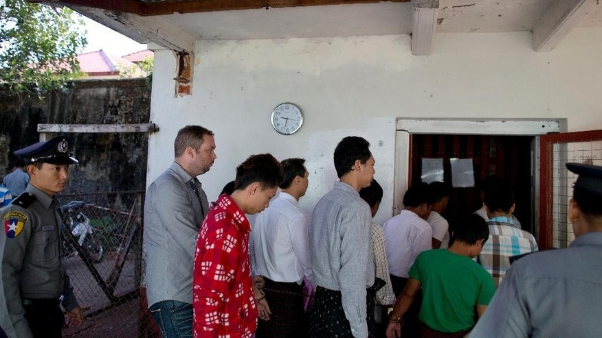 New Zealand citizen Philip Blackwood, second left, accused of insulting Buddhism, chained to other suspects of various crimes walk in to a transit cell ahead of a court hearing in Yangon, Myanmar, Thursday, Dec. 18, 2014. Blackwood and two Myanmar men have pleaded innocent to charges they insulted religion by posting an advertisement with an image of a pink Buddha wearing headphones. (AP Photo/Gemunu Amarasinghe)