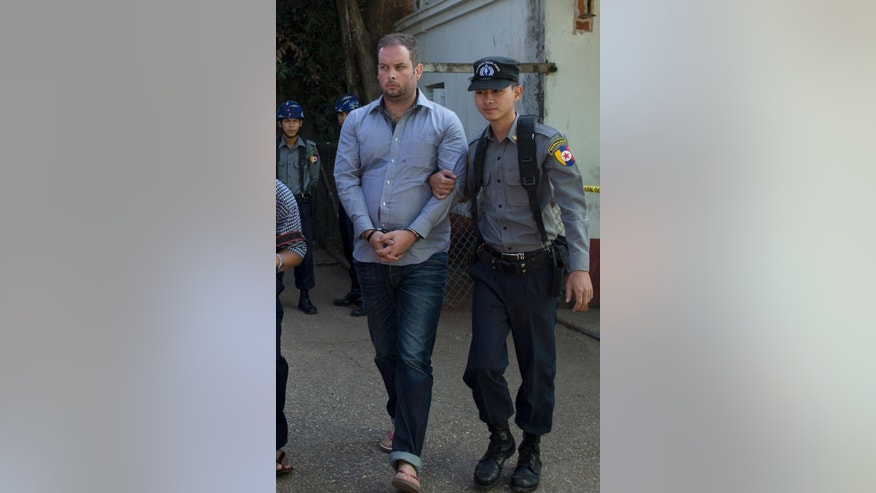 A police officer escorts New Zealand citizen Philip Blackwood, left, who is accused of insulting Buddhism, for a court hearing in Yangon, Myanmar, Thursday, Dec. 18, 2014. Blackwood, general manager of the V Gastro Bar, and two Myanmar business partners were arrested last week after posting an online advertisement for the tapas bar that showed a psychedelic image of Buddha wearing headphones. (AP Photo/Gemunu Amarasinghe)