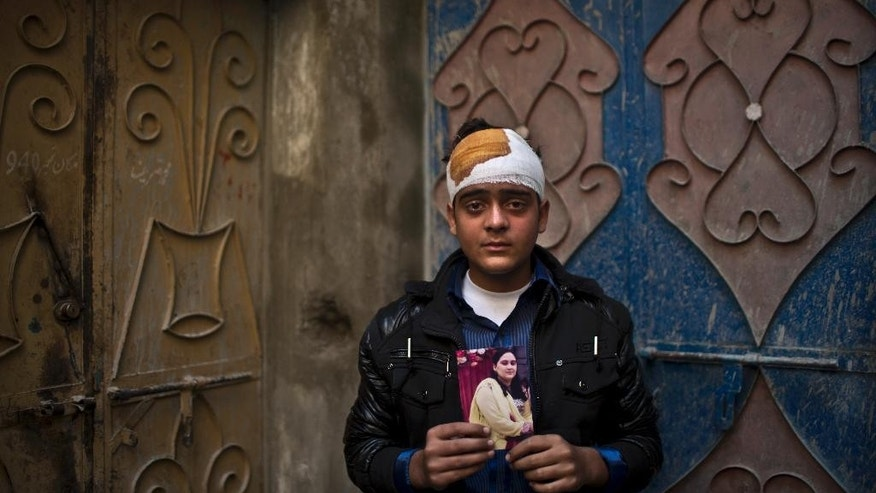 Pakistani student, Mohammad Baqair, who survived last Tuesday's Taliban attack on a military-run school and was slightly injured, poses for a picture holding a photograph of his mother a victim of the attack, who was a teacher at the school, at his home, in Peshawar, Pakistan, Thursday, Dec. 18, 2014. The Taliban massacre that killed more than 140 people, mostly children, at a military-run school in northwestern Pakistan left a scene of heart-wrenching devastation, pools of blood and young lives snuffed out as the nation mourned and mass funerals for the victims got underway. (AP Photo/Muhammed Muheisen)
