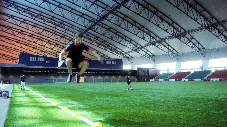 In this Nov. 6, 2014 photo, an athlete trains on the indoor pitch at the Aspire Academy in Doha, Qatar.  Qatar is relying on the academy to train what it hopes will be a competitive team at the World Cup it is hosting in 2022. (AP Photo/John Leicester).