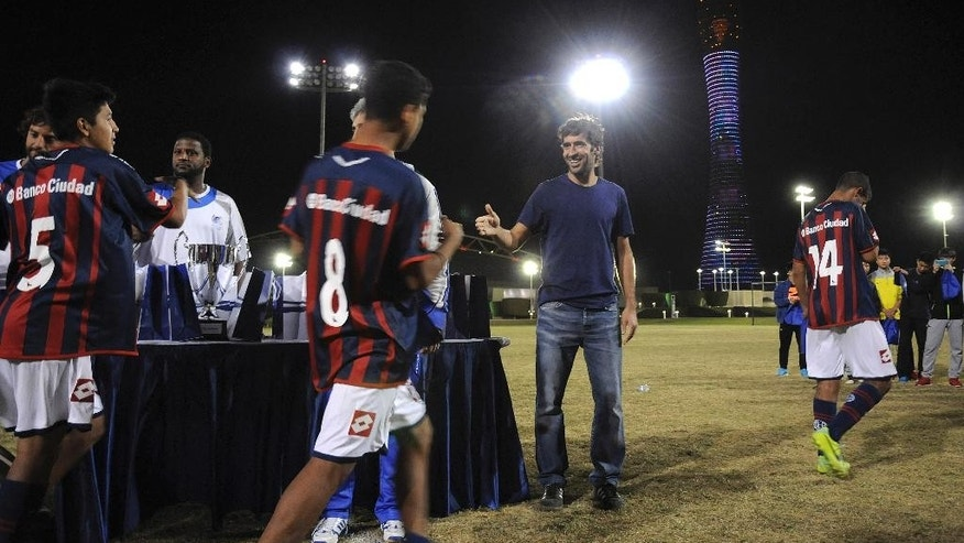 In this Nov. 5, 2014, former Real Madrid and Spain star Raul , centre, congratulates San Lorenzo players, as they play Qatar's Aspire Academy in Doha. Qatar is relying on the academy to train what it hopes will be a competitive team at the World Cup it is hosting in 2022. (AP Photo/John Leicester)