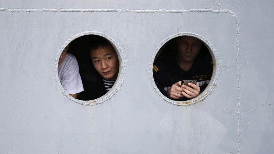 "Russian sailors peer from portholes of the Russian navy ship Smolny as it leaves the port of Saint-Nazaire, western France, Thursday, Dec.18, 2014. Russian sailors are leaving the French Atlantic port without the controversial French-made warship they were supposed to sail away on. France suspended the delivery of the ship to Russia ""until further notice"" last month because of the conflict in Ukraine. (AP Photo/Laetitia Notarianni)"