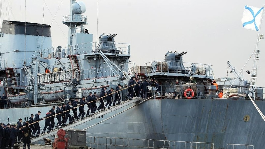 "Russian sailors embark the Smolny before leaving the port of Saint-Nazaire western France, Thursday, Dec.18, 2014. Russian sailors are leaving the French Atlantic port without the controversial French-made warship they were supposed to sail away on. France suspended the delivery of the ship to Russia ""until further notice"" last month because of the conflict in Ukraine. (AP Photo/Laetitia Notarianni)"