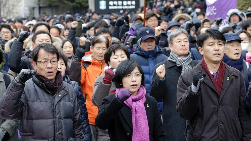 Lee Jung-hee, center, a head of the Unified Progressive Party, and supporters shout slogans against constitutional court's verdict near the constitutional court in Seoul, South Korea, Friday, Dec. 19, 2014. South Korea's constitutional court on Friday ordered the dissolution of the small leftist political party hounded by claims of pro-North Korea views. Critics say the decision could worsen already deep political divisions in a country once ruled by military dictators, and trigger a fierce debate on authorities' limits in restricting freedom of expression. (AP Photo/Lee Jin-man)