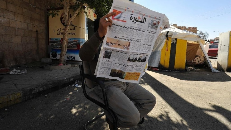 A Yemeni man reads al-Thawra newspaper outside their offices in Sanaa, Yemen, Wednesday. Dec. 17, 2014. Yemen's powerful Shiite rebels shut down a strategic Red Sea port on Wednesday, and stormed the offices of the country's main state newspaper, officials said. (AP Photo/Hani Mohammed)