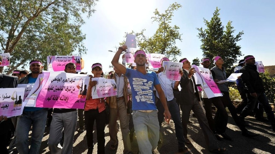 Students protest against the Shiite insurgency during a rally at the University of Sanaa, Yemen, Wednesday. Dec. 17, 2014. Yemen's powerful Shiite rebels shut down a strategic Red Sea port on Wednesday, and stormed the offices of the country's main state newspaper, officials said. (AP Photo/Hani Mohammed)