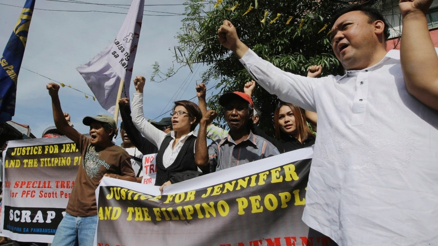 Dec. 19, 2014: Lawyers for the prosecution Harry Roque, right, and Virgie Suarez, second from left, join other protesters after the convoy of vehicles transporting US Marine PFC Joseph Scott Pemberton left the court following his appearance for the first time