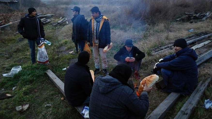 In this photo taken Monday, Dec. 15, 2014, migrants gather around the fire which they use for cooking and warmth in the abandoned brick factory in the northern Serbian town of Subotica, near the border between Serbia and Hungary. Coming from as far away as Afghanistan and Syria and as near as Kosovo and Albania, thousands of irregular migrants a week are crossing into Hungary and requesting asylum, turning the country into a new hot spot in a transit route into the EU. (AP Photo/Darko Vojinovic)