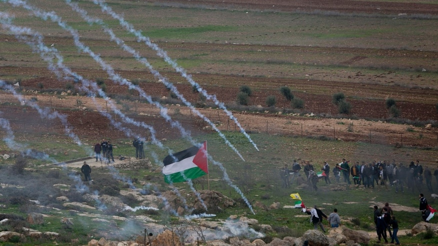 Dec. 19, 2014 - Israeli troops fire tear gas toward Palestinian protesters near a village outside of Ramallah. Clashes erupted between Palestinian protesters and Israeli forces at a West Bank military checkpoint near Turmus Aya. A rocket fired from the Gaza Strip struck southern Israel on Friday, the Israeli military said, in the first such attack since September.