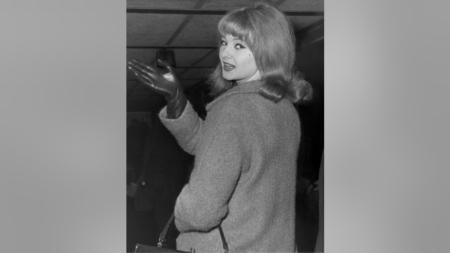 "FILE - In this Jan. 7, 1964 file photo, Mandy Rice-Davies waves goodbye at London Airport as she leaves for Munich for a singing engagement. Mandy Rice-Davies, a key figure in Britain's biggest Cold War political scandal, the ""Profumo Affair,"" has died. She was 70. Her PR firm said Friday Dec. 19, 2014, that Rice-Davies died Thursday evening ""after a short battle with cancer."" (AP Photo/File)"