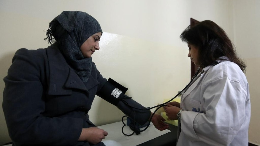 In this Wednesday, Dec. 10, 2014 photo, Hoda Barakat, right, a registered midwife, takes the blood pressure of Syrian Manal Allan, 24, at a natal clinic in Beirut, Lebanon. Nearly 30,000 Syrian children born as refugees in Lebanon are in a legal limbo, not registered with any government, exposing them to the risk of a life of statelessness deprived of basic rights. (AP Photo/Bilal Hussein)