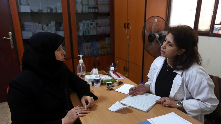 In this Wednesday, Dec. 10, 2014 photo, Hoda Barakat, right, a registered midwife, speaks with Syrian Wafaa Daaboul, 45, at a natal clinic in Beirut, Lebanon. Nearly 30,000 Syrian children born as refugees in Lebanon are in a legal limbo, not registered with any government, exposing them to the risk of a life of statelessness deprived of basic rights. (AP Photo/Bilal Hussein)