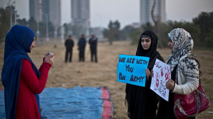 Dec. 19, 2014 - A Pakistani university student takes a picture of her friends holding banners prior to a protest condemning Tuesday's Taliban attack on a military-run school in Peshawar, in Islamabad, Pakistan that left 148 dead. Pakistani warplanes and ground forces killed at least 77 militants in a northwestern tribal region near the Afghan border.