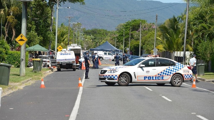 Police block the road outside a house where eight children have been found dead the Cairns suburb of Manoora, Australia, Friday, Dec. 19, 2014. Police said when they got to the house, they found the bodies of the children inside the home. The victims range in age from 18 months to 15 years.(AP Photo/Graeme Bint)