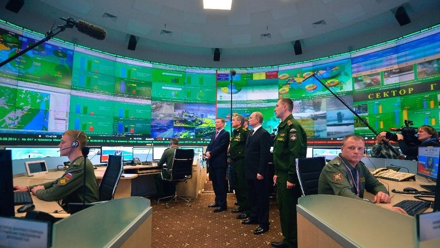 Russian President Vladimir Putin, second right, stands with Defense Minister Sergei Shoigu, third right, and presidential chief of staff Sergei Ivanov, left, and listens to an explanation in the Defense Ministry control room during a meeting with senior military officials in Moscow, Russia on Friday, Dec. 19, 2014. (AP Photo/RIA Novosti, Alexei Druzhinin, Presidential Press Service)