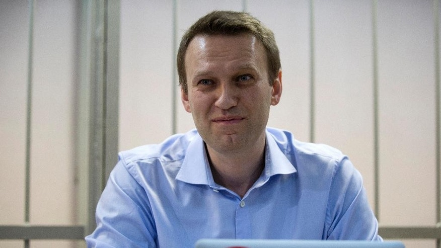 "Russian opposition activist and anti-corruption crusader Alexei Navalny smiles in a court room in Moscow, Russia, Friday, Dec. 19, 2014. Opposition activist and anti-corruption blogger Alexei Navalny, who has been under house arrest since February, is being charged in a second trial that may put him behind bars for good. A laptop in front of Navalny has a sticker with a portrait of Russian President Vladimir Putin in the bottom of word ""Thief"", right. (AP Photo/Pavel Golovkin)"