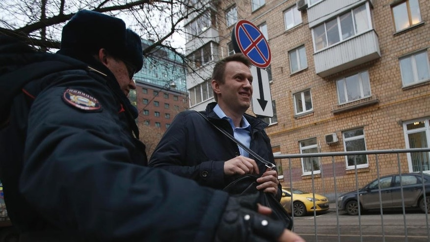 A police officer inspects Alexei Navalny, center, before letting him in a Moscow court, Russia, Friday, Dec. 19, 2014. Opposition activist and anti-corruption blogger Alexei Navalny, who has been under house arrest since February, is being charged in a second trial that may put him behind bars for good.  (AP Photo/Pavel Golovkin)