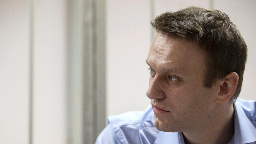 Russian opposition activist and anti-corruption crusader Alexei Navalny waits for a start of a trial in a court room in Moscow, Russia, Friday, Dec. 19, 2014. Opposition activist and anti-corruption blogger Alexei Navalny, who has been under house arrest since February, is being charged in a second trial that may put him behind bars for good. (AP Photo/Pavel Golovkin)