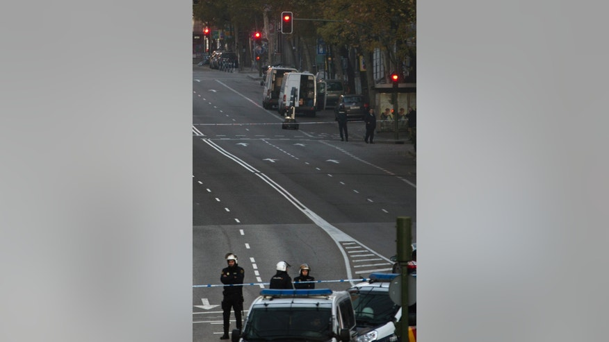 Spanish police cordon off streets around the headquarters of the ruling conservative Popular Party as they are searching for possible explosives after a man rammed his car into the building in Madrid, Spain, Friday, Dec. 19, 2014. A police spokeswoman said bomb disposal experts found two gas cylinders in the car and an unidentified substance. Leading Cadena SER radio cited police as saying said the man admitted attacking the party headquarters Friday because he had lost his business in the economic crisis. (AP Photo/Paul White)