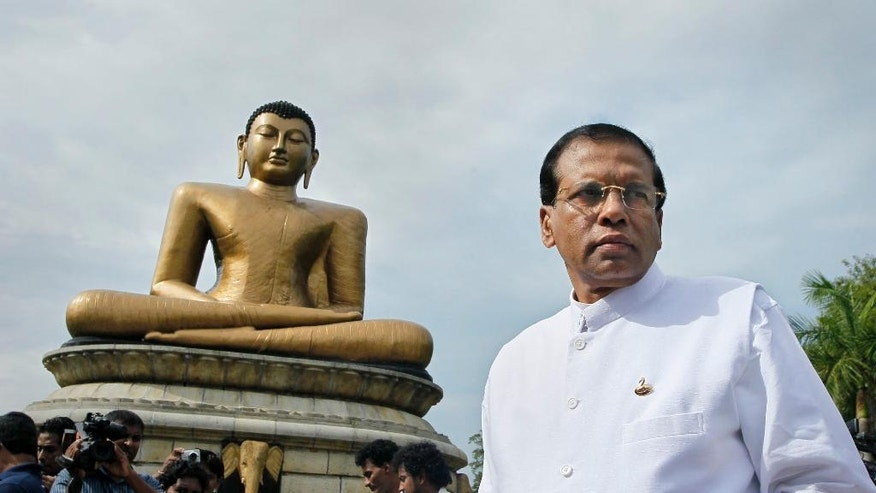 Sri Lankan main opposition presidential candidate Maithripala Sirisena arrives to launch of his election manifesto in Colombo, Sri Lanka, Friday, Dec. 19, 2014. Sirisena said Friday that the country cannot be charged with war crimes in the International Criminal Court, but he will launch a domestic inquiry if he wins a January election. (AP Photo/Eranga Jayawardena)