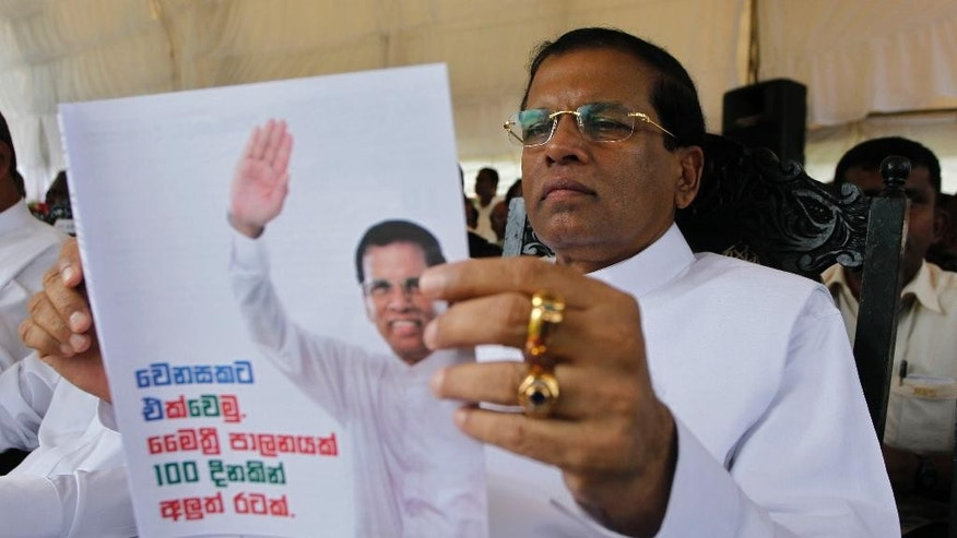 "Sri Lanka's main opposition presidential candidate Maithripala Sirisena speaks during the launch of his election manifesto in Colombo, Sri Lanka, Friday, Dec. 19, 2014. Sirisena said Friday that the country cannot be charged with war crimes in the International Criminal Court, but he will launch a domestic inquiry if he wins a January election. Writing in Sinhalese writes ""Gather for a change. Maithri regime. New country in a hundred days.""  (AP Photo/Eranga Jayawardena)"