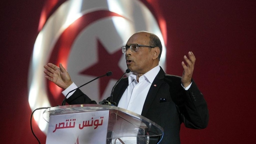Tunisian President Moncef Marzouki, gestures as he speaks during a campaign meeting in Tunis, Tunisia, Sunday, Dec. 14, 2014. Tunisian President Moncef Marzouki will face Nidaa Tounes party leader Beji Caid Essebsi in the presidential runoff on December 21. Inscription reads, 'Tunisia will win'. (AP Photo/Aimen Zine)